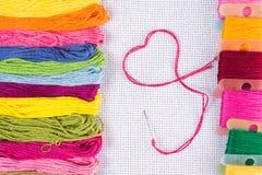Gekleurde draad voor borduurwerk op wit canvas, een naald met rode draad in de vorm van een hart Het concept liefde voor een hobb Royalty-vrije Stock Afbeeldingen