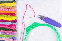 Gekleurde draad voor borduurwerk op wit canvas, een naald met rode draad en een Hoepel Exemplaarspase stock foto