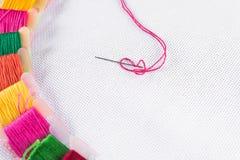 Gekleurde draad voor borduurwerk op wit canvas, een naald met rode draad Exemplaarspase royalty-vrije stock afbeelding