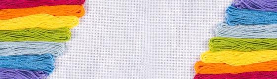 Gekleurde draad voor borduurwerk op wit canvas Exemplaarspase stock foto
