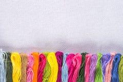 Gekleurde draad voor borduurwerk op wit canvas Exemplaarspase royalty-vrije stock foto