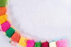 Gekleurde draad voor borduurwerk op wit canvas Exemplaarspase stock foto's