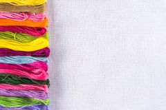 Gekleurde draad voor borduurwerk op wit canvas Exemplaarspase stock afbeelding