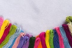Gekleurde draad voor borduurwerk op wit canvas Exemplaarspase stock fotografie