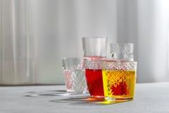 Gekleurde dranken in glaskoppen op een grijze achtergrond stock afbeeldingen
