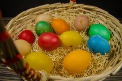 Gekleurde eieren in rieten mand stock afbeeldingen
