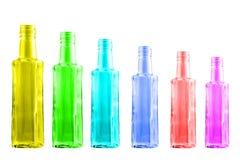 Gekleurde flessen die zich op een rij op een witte achtergrond bevinden Stock Afbeeldingen
