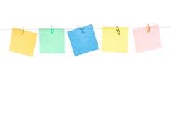 Gekleurde gele, groene, blauwe, rode stickers met paperclippen die op een kabel hangen Stock Afbeeldingen