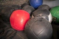 Gekleurde geneeskrachtige die gymnastiekballen in een hoek worden gestapeld stock afbeelding