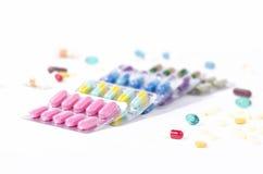 Gekleurde geneeskunde in verscheidene blaarpakken met verspreide pillen Stock Afbeeldingen