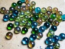 Gekleurde glasballen die op een houten oppervlakte worden verspreid stock fotografie