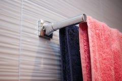 gekleurde handdoeken die op het rek in de badkamers hangen, blauw en roze, paar, familieconcept royalty-vrije stock afbeeldingen