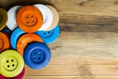 Gekleurde knopen op houten raad, Kleurrijke knopen, op oude houten Royalty-vrije Stock Afbeeldingen