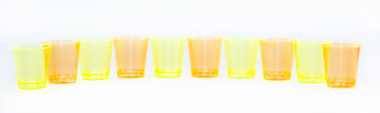 Gekleurde koppen die naast elkaar op een witte geel en oranje achtergrond worden opgesteld - Royalty-vrije Stock Afbeeldingen