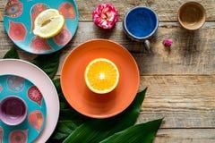 Gekleurde koppen en platen dichtbij tropische bladeren en vruchten op houten hoogste mening als achtergrond copyspace stock foto's