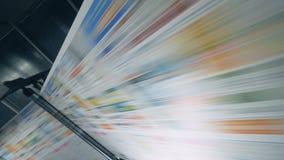 Gekleurde krant die op een typografietransportband rollen, geautomatiseerde machine stock video