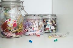 Gekleurde linten en kleurrijke knopen in glaskruiken voor het creëren van artistieke hobbys stock foto