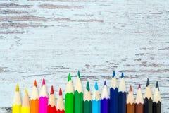 Gekleurde multicolored potloden dicht omhoog macro neer op een uitstekende houten achtergrond, houten versleten raad met barsten Stock Afbeeldingen
