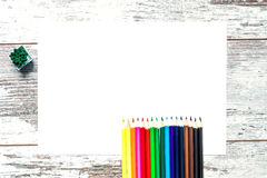 Gekleurde multicolored potloden, een blad van Witboek op een uitstekende houten achtergrond, houten versleten raad met barsten Stock Foto's