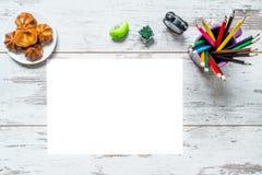 Gekleurde multicolored potloden, een blad van Witboek, oude stijlklok, plaat met cake op een uitstekende houten achtergrond Stock Fotografie