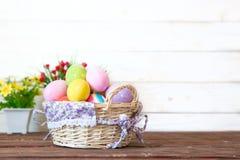 Gekleurde paaseieren in de mand en de lentebloemen op houten achtergrond De kaart van de groet royalty-vrije stock afbeelding