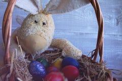 Gekleurde paaseieren in het de mand en Pasen-Konijntje Stock Afbeelding