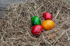 4 gekleurde paaseieren legt in het droge hooi op de houten oude raad stock foto's