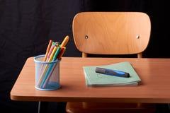 Gekleurde Pennen in een blauwe metaalmand op bureau in school stock afbeeldingen