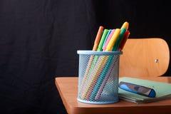 Gekleurde Pennen in een blauwe metaalmand op bureau in school stock fotografie