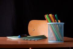 Gekleurde Pennen in een blauwe metaalmand op bureau in school royalty-vrije stock afbeelding