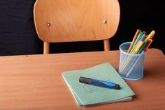 Gekleurde Pennen in een blauwe metaalmand op bureau in school royalty-vrije stock foto