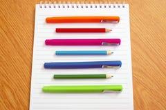 Gekleurde pennen op een blocnote Stock Foto