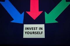 Gekleurde pijlen met document sticker voor textspase op donkerblauwe achtergrond Investeer in zich stock foto