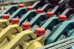 Gekleurde plastic blikken met motorolie Rijen van bussen op een pallet worden geplaatst die royalty-vrije stock foto's