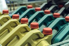 Gekleurde plastic blikken met motorolie Rijen van bussen op een pallet worden geplaatst die royalty-vrije stock fotografie