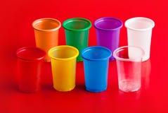 Gekleurde plastic glazen op rode achtergrond Stock Foto