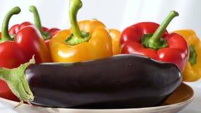 Gekleurde rode gele die Groene paprika en aubergine op plaat wordt geplaatst stock footage