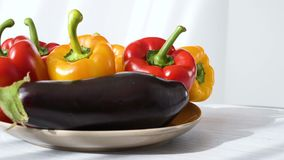 Gekleurde rode gele die Groene paprika en aubergine op plaat wordt geplaatst stock video