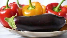 Gekleurde rode gele die Groene paprika en aubergine op plaat wordt geplaatst stock videobeelden
