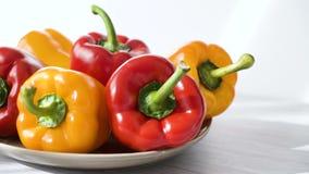 Gekleurde rode gele die Groene paprika op plaat wordt geplaatst stock videobeelden