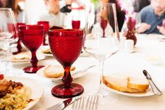 Gekleurde rode steenglazen en lege wijnglazen op de lijst Vage mensen op achtergrond Royalty-vrije Stock Foto's