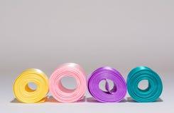 Gekleurde rollen van de linten van het zijdesatijn op grijs Stock Foto