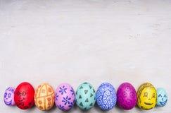 Gekleurde siereieren voor Pasen met geschilderde gezichten dicht omhoog grens, plaats voor tekst houten hoogste mening rustieke a Stock Foto's