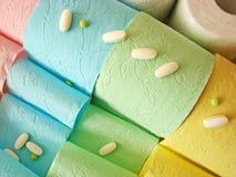 Gekleurde toiletpapier en pillen op het stock fotografie