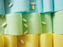 Gekleurde toiletpapier en pillen op het royalty-vrije stock afbeelding