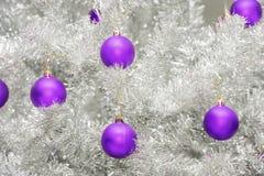 In gekleurde ultraviolette snuisterijen op zilveren kunstmatige Kerstmisboom Royalty-vrije Stock Afbeeldingen