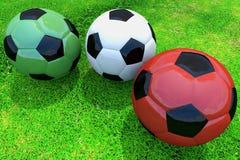 Gekleurde voetbalballen op gras Royalty-vrije Stock Afbeeldingen