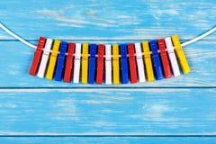 Gekleurde wasknijpers die op een kabel hangen Royalty-vrije Stock Afbeelding