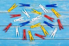 Gekleurde wasknijpers op een blauwe achtergrond Stock Afbeeldingen