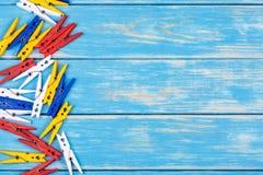 Gekleurde wasknijpers op een blauwe achtergrond Stock Fotografie